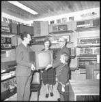 10057 Overhandiging in een radio- en televisiewinkel van een televisieapparaat aan gezinsleden.