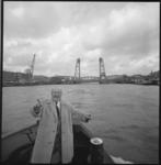 10111-2 Zanger Albert de Booij (1897-1971) op de voorplecht van een bootje dat door op de Nieuwe Maas vaart ter hoogte ...