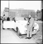 10177 De Franse zanger Charles Aznavour staat voor een auto bij de hoofdingang van het Hilton-hotel aan de Kruiskade.