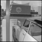 10182-1 Een automobilist op het Schouwburgplein gaat parkeerkaartje in automaat steken. Op de achtergrond: de ...