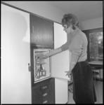 10227-1 Dame in Skyway Hotel aan de Vliegveldweg staat in hotelkamer bij geopende koelkast.