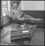 10251 Sigaretrokende dame ligt op bank in huiskamer tijdschrift te lezen met op de voorgrond een bandrecorder met spoelen.