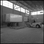 10312 In een bedrijfsloods wordt de inhoud van een container gelost.