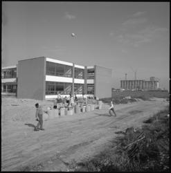 10318 Spelende kinderen in de nieuwbouwwijk Ommoord. Op de achtergrond een schoolgebouw.