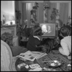 10498 Enkele mensen zitten in huiskamer met een kat naar de televisie te kijken.