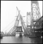 10519 Het beweegbare brugdek van de Spijkenisserbrug hangt in de takels van hefbokken, naast de brug.