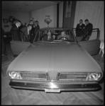 10530-1 Mannen bekijken een Chrysler-auto in de tentoonstellingszaal.