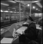 10565-2 Man bedient apparatuur in controlepost in metrostation Zuidplein.