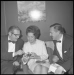 10614 Mrs. Evelyn Ritchey, public relations-manager van Hilton-Benelux-hotels, bekijkt samen met twee heren in smoking, ...