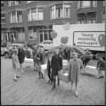10673 Schooljeugd sjouwt met dozen; op de achtergrond een vrachtwagen met de slogan 'snoep verstandig eet 'n appel'
