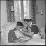 10975-2 Verpleegkundige helpt een bewoner in bed met drinken uit een kopje.