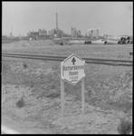 11047 Havenroutebord met petrochemische bedrijven in de achtergrond.