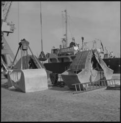 11122 Twee zandgrijpers liggen los op de kade, met schip op de achtergrond.