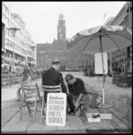 11125 Schoenpoetser aan het werk op de Lijnbaan met stadhuis in de achtergrond.