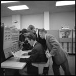 11144 Vier mannen overleggen met elkaar in een ruimte met electronische opslagsystemen.