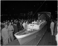 1117 Veel belangstellenden rond het model van ss Statendam bij het verlaten van een loods en op weg naar een ...