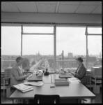 11222 Twee dames bij typemachines op een afdeling van de Gemeentelijke Sociale Dienst aan de Oostzeedijk 200. Op de ...