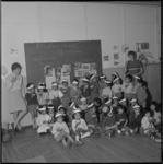 11225 Groepsfoto van Ambonese kinderen met hun begeleidsters in de kleuterschool in het houten barakkenkamp ...