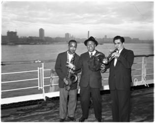 1124 Drie jazzmusici met instrumenten op dek van schip. In het midden bandleider Lionel Hampton.