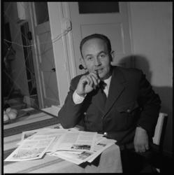 11268 Tramconducteur en auteur/fotograaf/zanger Frits J. van Zonneveld in RET-uniform bij wat publicaties, in een huiskamer.