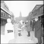 11330 Een kerstman en een sneeuwman nemen geschenken in ontvangst, bestemd voor het geestelijk ernstig gehandicapte kind.