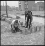11336 Stratenmakers op Ammanplein bezig met trottoirtegels. Op de achtergrond de Nieuwe Oosterkerk aan de Boezemweg 170.