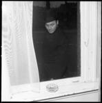 11338 Man kijkt naar asbak in een vensterbank.