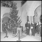 11339-1 In de hal van het stadhuis staat de door Noorwegen geschonken kerstboom opgesteld; rechts burgemeester W. ...