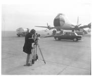11392 Man filmt op platform van Zestienhoven; met auto en een vliegtuig van British Air Ferries (BAF) op de achtergrond.