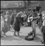 11535 Op het Binnenwegplein ter hoogte van de firma Jungerhans werpt een mevrouw iets in de gitaarkist van een spelende ...