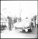 11590-1 Wethouder R. Langerak zwaait met de vlag bij één van de deelnemende auto's aan de Tulpenrallye.