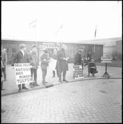 11590-2 Demonstranten protesteren met tekstborden tegen de Tulpenrallye, voor het Bureau Parkeercontrole.