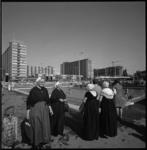 11668-2 Dames in klederdracht lopen bij waterbassin op het Schouwburgplein; met Olveh-flats op de achtergrond.