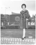11719-1 Dame showt bontmantel op Schouwburgplein, ter hoogte van de Pauluskerk.