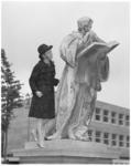 11719-2 Modeshow-achtige dame staat met bontmantel bovenop de sokkel van het standbeeld van Erasmus.