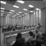 11753 Internationale telefoonzaal PTT aan de Coolsingel, geheel gevuld met personeel en apparatuur.