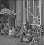 11872 Mensen zitten op terras van Noordzee-Quick-restaurant bij een ingang van het Beursgebouw op het Beursplein.