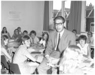 11883 De heer P. van der Ree, wiskundeleraar aan de christelijke mavo Prinses Julianaschool, temidden van leerlingen.