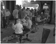 11884 Kinderen zitten te lezen tijdens de rommelmarkt Binnenrotte onder het spoorwegviaduct tussen Meent en Hoogstraat.