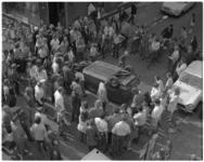 11918-2 Hoog overzicht van kruispunt in Oude Westen waar wijkbewoners een op zijn kop liggende auto bekijken.