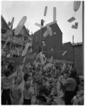 11919 Kinderen laten ballonnen van het Rotterdams Nieuwsblad op, temidden van huizen en achtertuinen.