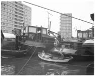 11937 In een roeiboot naast afgemeerde binnenvaartschepen zitten jongens te vissen in het Boerengat.