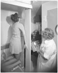 11999-2 Dame, geknield in het mobiele consultatiebureau tegen een onderzoeksapparaat, onder toeziend oog van een ...