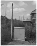 12335 Een ca. 3 meter hoge paal en een systeemkast; met schoorstenen van Vondelingenplaat op de achtergrond.