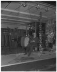 12654 Man zit op stoel in etalage en bewaakt spullen nadat ruit van filiaal van de Mantelspecialist aan de Lijnbaan was ...