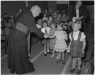 132 Deken mgr. J.H.Niekel begroet kinderen.