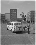 13334 Engelse reclametaxi Mary Quant op Grotekerkplein voor standbeeld Erasmus.