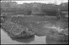 1372-3 Transport van zinkstukken voor het Noordereiland in de Koningshaven. Op de achtergrond de Koninginnebrug en het ...
