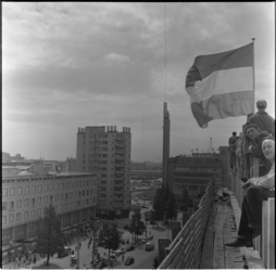 15 Vlag op Bijenkorf-in-aanbouw bij bereiken hoogste punt; Coolsingel; HBU-gebouw en oude Bijenkorf op de achtergrond.