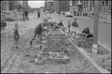 1683-1 Kinderen bouwen huisjes van straatklinkers op de Schiekade.